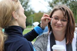 Walk participants apply NEDA logo fake tattoos on their cheeks.