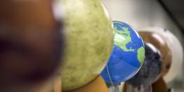 A blue and green Earth globe within a row of globes