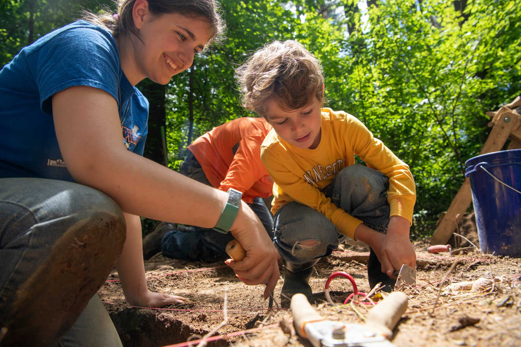 A student and young child dig in Wayne Nation Forest for archaeological specimen