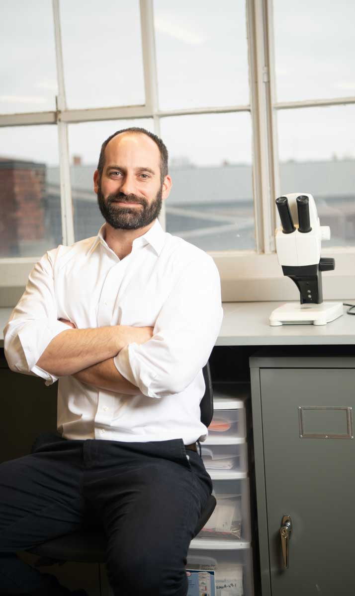 Assistant professor of anthropology, Joseph Gingerich, poses in his lab next to a microscope.