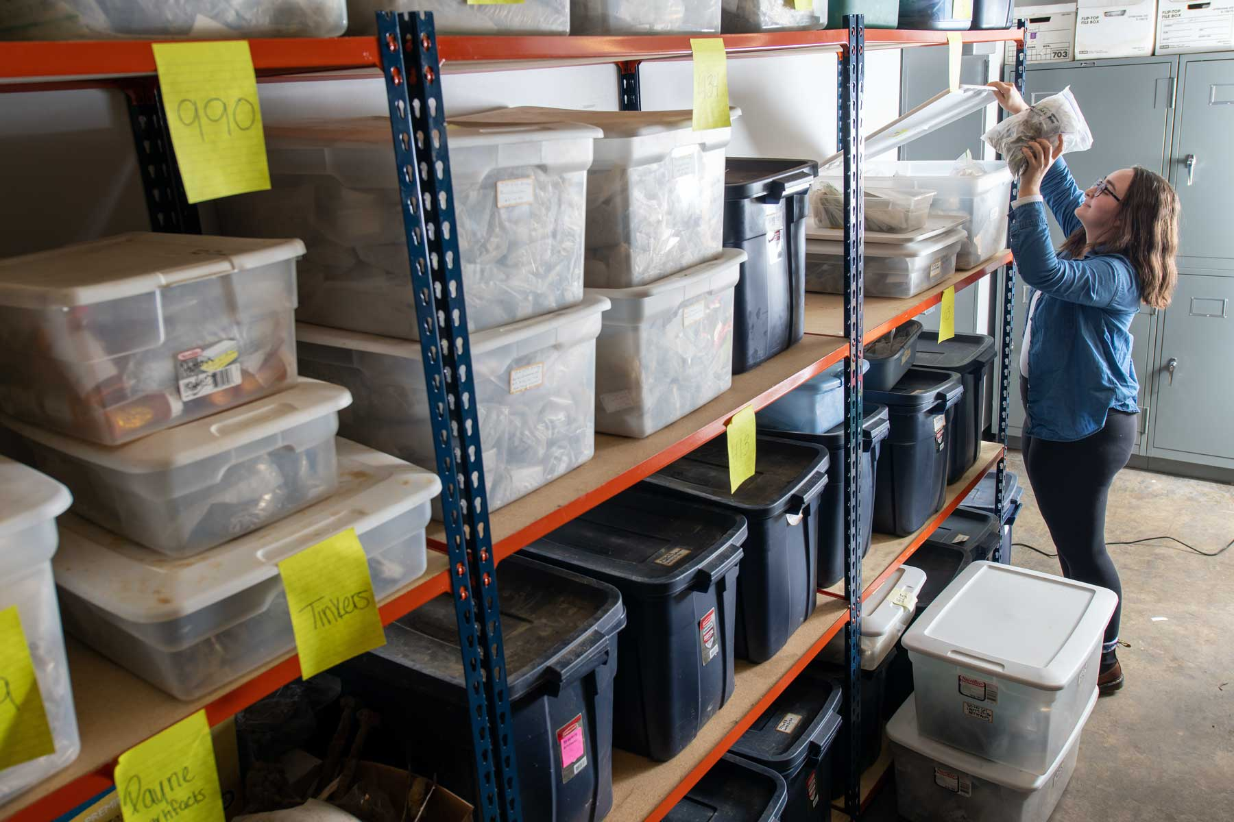 A student accessses stacks of boxes filled with categorized archaeological specimens