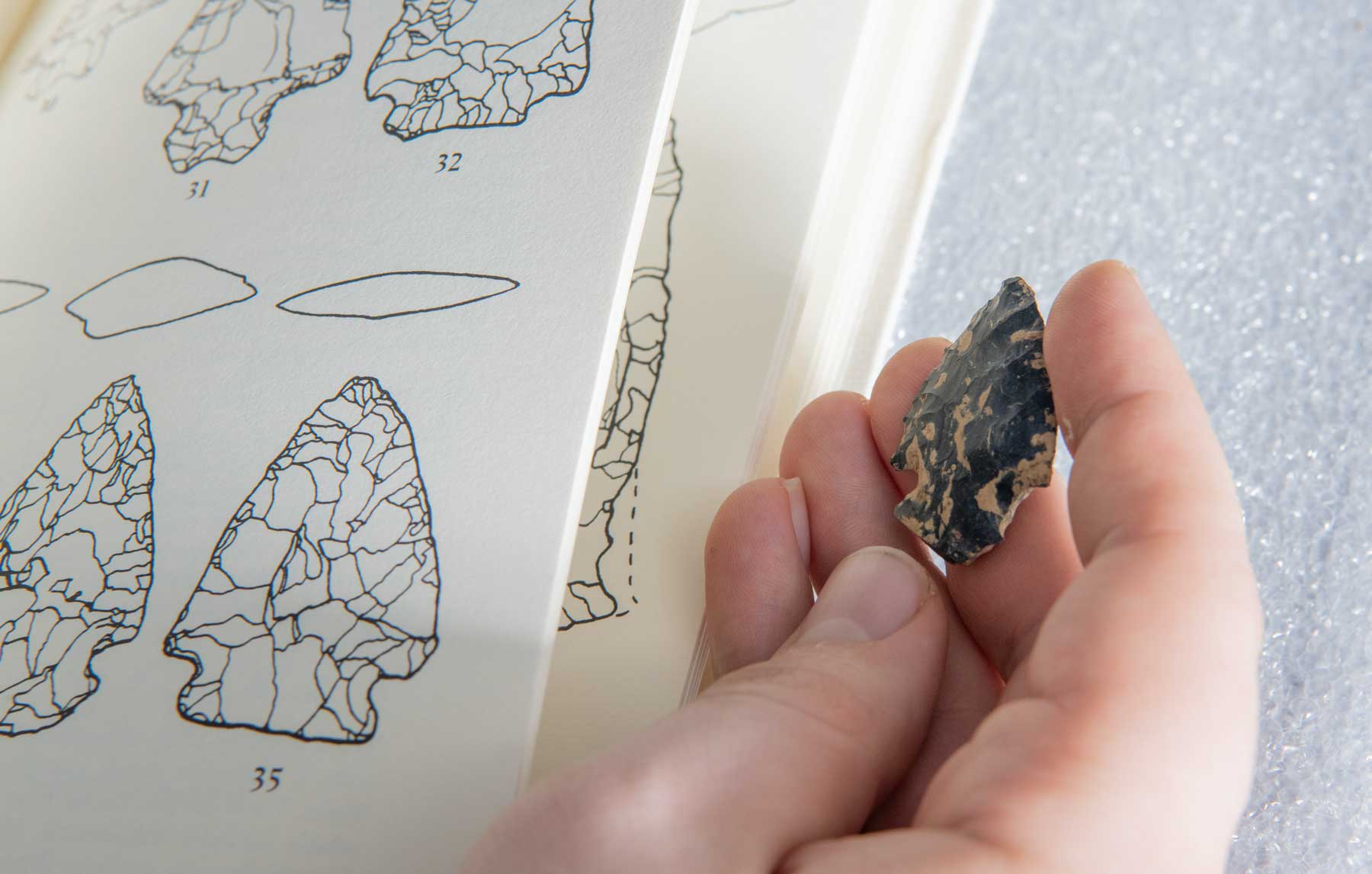 Image of an arrowhead identification book next to a stone arrowhead in a person's hand