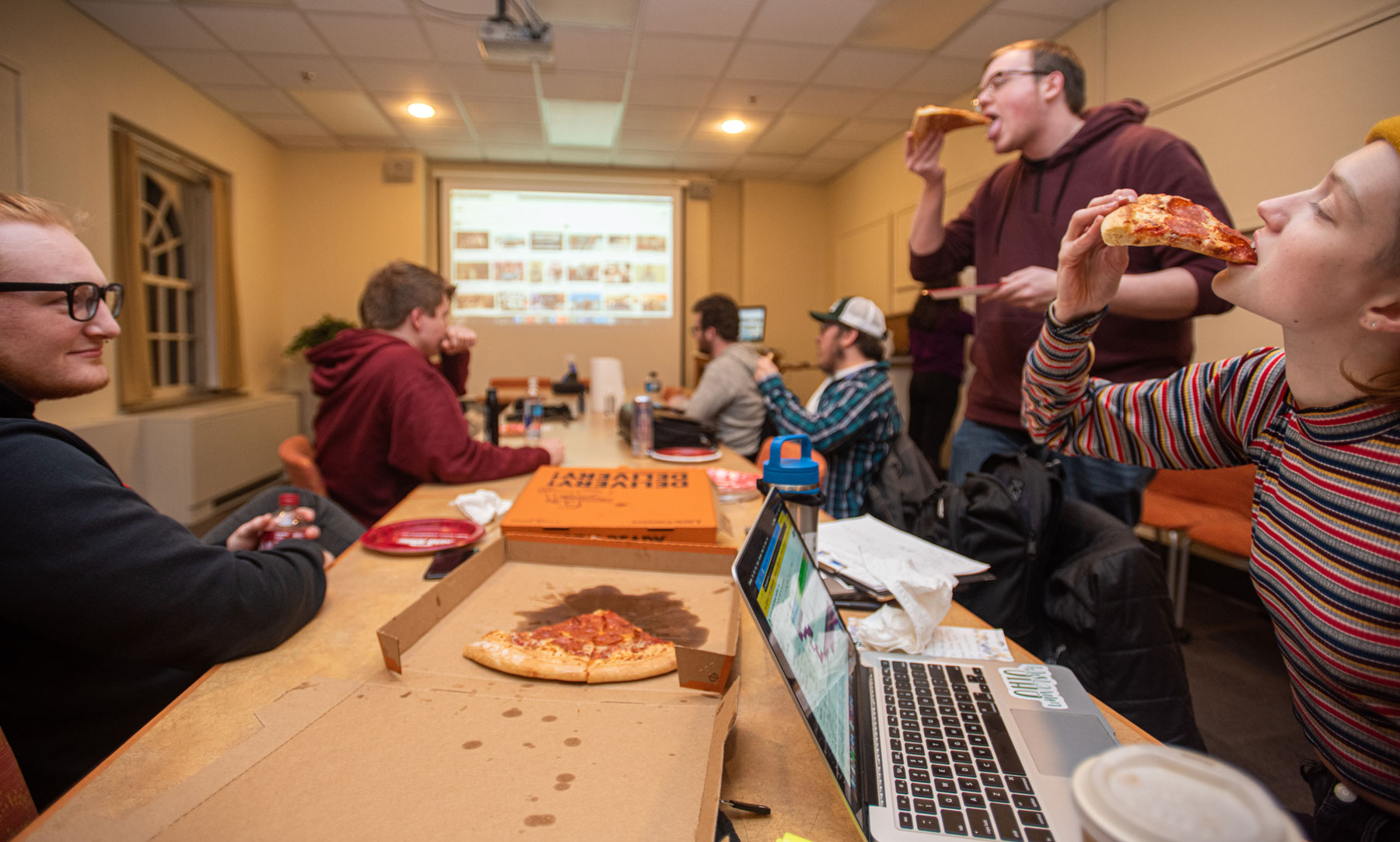 Students enjoying pizza during a planning session