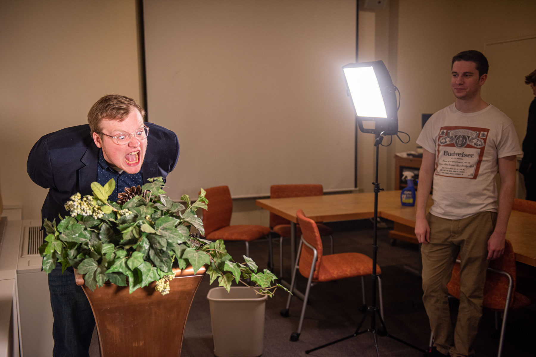 A man illuminated by video lighting shouting at a plant