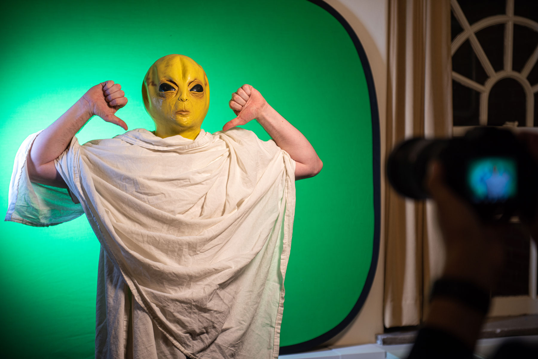 A person in an alien mask poses in front of a video green screen