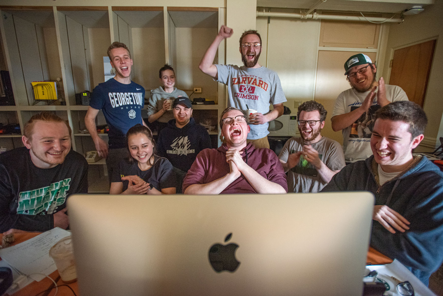 Student team celebrating around a Macintosh computer