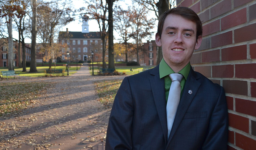 "Mitchell ""Mitch"" Holland, BBA '19, is pictured on Ohio University's College Green with Cutler Hall in the background."
