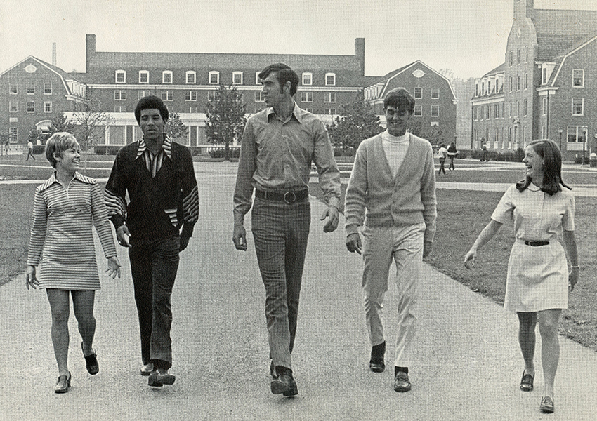 Ohio University Men's Basketball players (from left) Tom Corde, Craig Love and Bob Howell are seen walking on West Green with two of the University's cheerleaders.