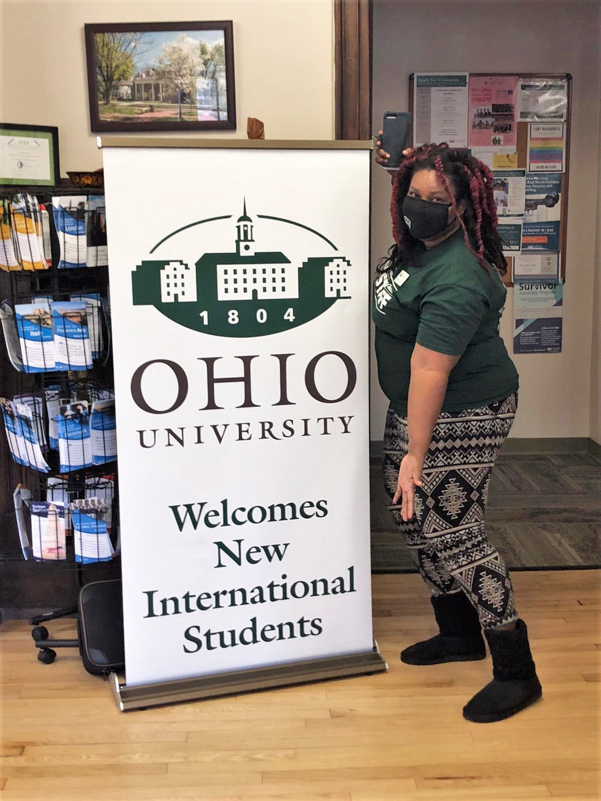 Shauna Torrington poses by sign that reads Ohio University Welcomes New International Students