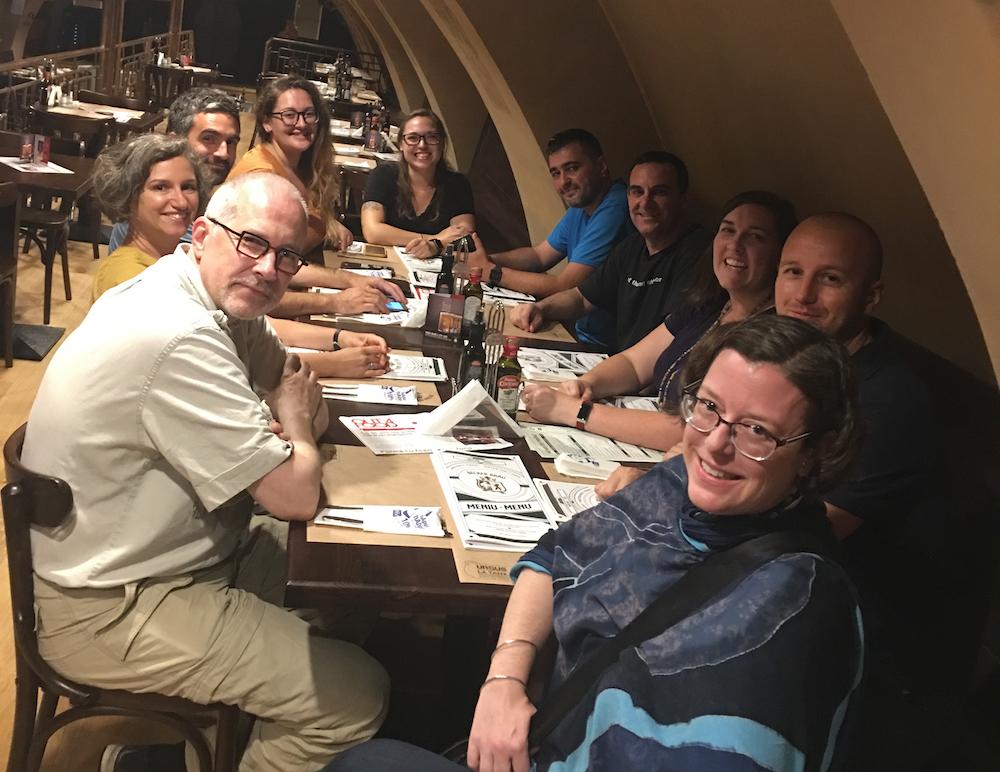 Dr. Sabrina Curran și o echipă internațională care lucrează în România stau în jurul unei mese într-un restaurant
