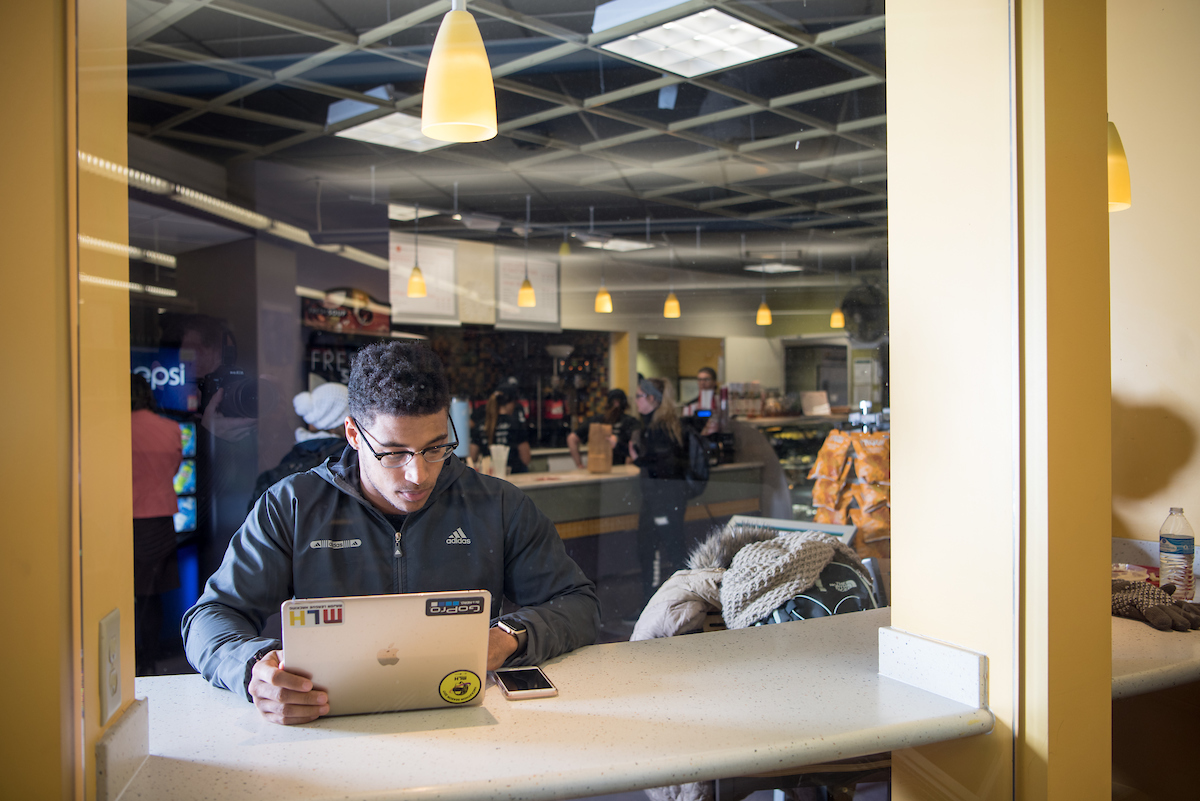 Student studying on his laptop in a cafe