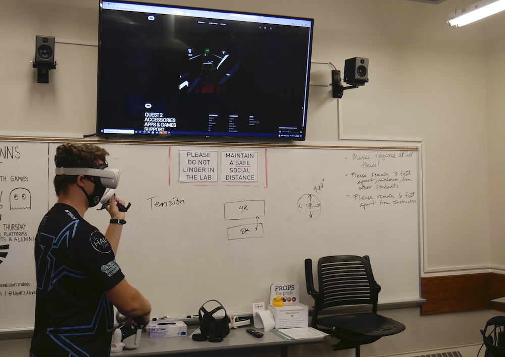A student stands in a classroom in front of a whiteboard wearing a VR headset.  What the student sees through the headphones is displayed on a television set above the whiteboard.