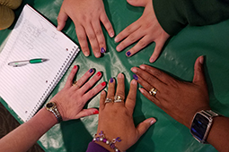 A volunteer paints ring fingers purple in support of the #PutTheNailInIt campaign to end domestic violence.