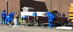 Students in hazardous materials jumpsuits and hoods assess a suspected chemical spill during a critical incident response scenario Friday at the Collins Career Technical Center.