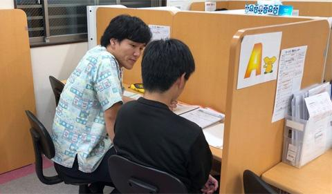 Nakada helping a student at their desk