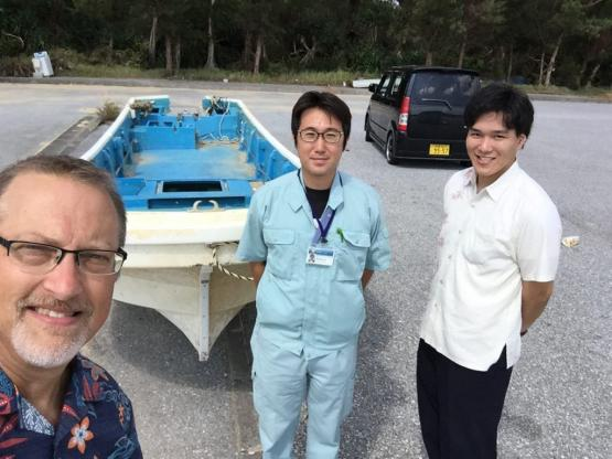 Thompson takes a selfie with Yonashiro and Nakada, with the washed up boat behind them in a parking lot