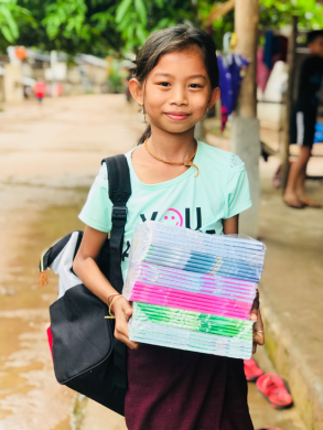 little girl carrying notebooks and a backpack